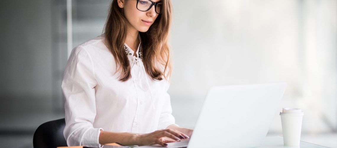 successful businesswoman working on laptop computer in her office dressed up in white strict clothes