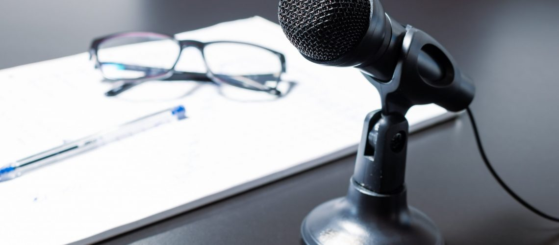 Small black desk microphone with cable and low stand on a black table next to notepad, glasses and glasses. Modern style, Communication and speech concept.